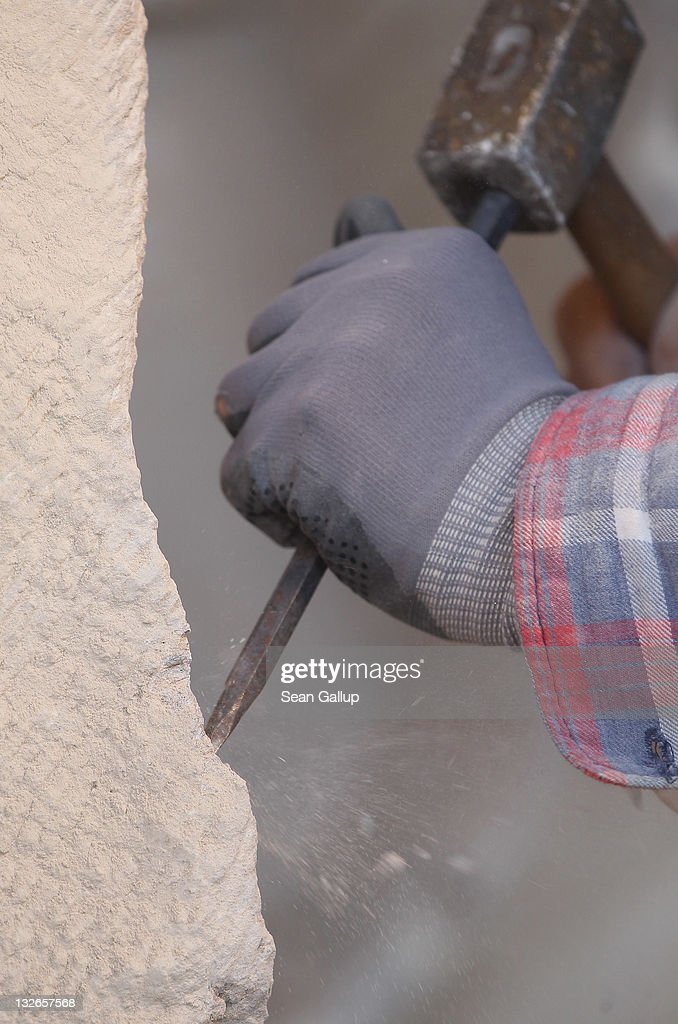 Stone sculptor Carlo Wloch hammers a chisel into sandstone as he copies a gabel decoration at the Schlossbauhuette studio, where Wloch and a team of sculptors are creating decorative elements for the facade of the Berliner Schloss city palace on November 11, 2011 in Berlin, Germany. The Berliner Schloss was the residence of the Prussian Kaiser and was among the major architectural landmarks of Berlin until it was heavily damaged by Allied bombing in 1945. The communist authorities of East Berlin demolished the building in the 1950s, and today's Berlin government is pursuing an ambitious project to rebuild the palace according to a design by Italian architect Franco Stella, which will recreate the facade of the building but with a modern interior at a cost of approximately EUR 590 million. The Humboldt Forum, the foundation leading the project, has given the Schlossbauhuette sculptors the formidable task of recreating the hundreds of architectural elements that decorated the facade, and though some original pieces were saved, more often the sculptors have only old black and white photos as reference.