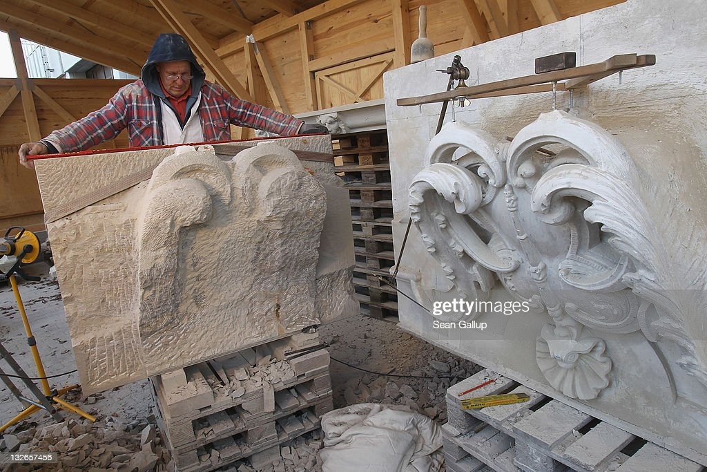 Stone sculptor Carlo Wloch measures a sandstone block that he is chiseling into a gabel decoration according to a plaster cast (R) at the Schlossbauhuette studio, where Wloch and a team of sculptors are creating decorative elements for the facade of the Berliner Schloss city palace on November 11, 2011 in Berlin, Germany. The Berliner Schloss was the residence of the Prussian Kaiser and was among the major architectural landmarks of Berlin until it was heavily damaged by Allied bombing in 1945. The communist authorities of East Berlin demolished the building in the 1950s, and today's Berlin government is pursuing an ambitious project to rebuild the palace according to a design by Italian architect Franco Stella, which will recreate the facade of the building but with a modern interior at a cost of approximately EUR 590 million. The Humboldt Forum, the foundation leading the project, has given the Schlossbauhuette sculptors the formidable task of recreating the hundreds of architectural elements that decorated the facade, and though some original pieces were saved, more often the sculptors have only old black and white photos as reference.