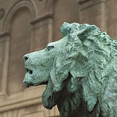 Stone sculpture of a lion in front of a building