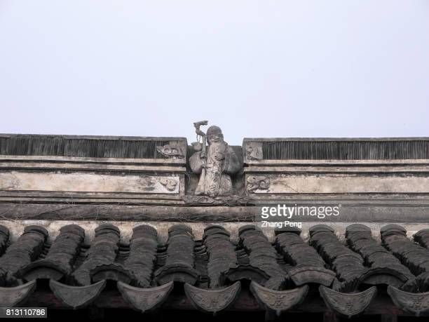 Stone sculpture of the god of longevity stands on the black tiled roof is a tradition in Chinese architecture The Retreat Reflection Garden built in...