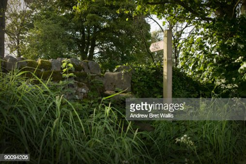 A stone stile and footpath sign in the countryside : Stock Photo