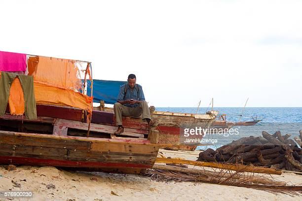 Stone Town, Zanzibar: Man on Beach Looking at Phone