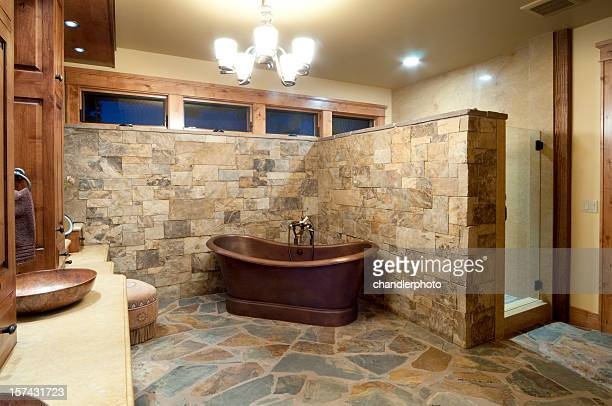 Stone wall and floor bathroom with brown freestanding bath