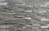 Stone wall cladding made of horizontal gray, brown and white strips of rock stacked . Background and texture