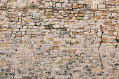 Old stone wall texture. Fortified stone wall of an ancient fortress from the Roman Empire.