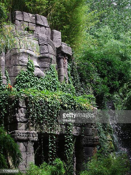 Stone-faced statue in the jungle surrounded by trees