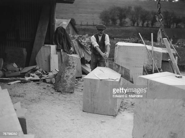 A stonemason uses a frigbob to cut a block of Bath stone at a masonry yard in Corsham Wiltshire 24th October 1928