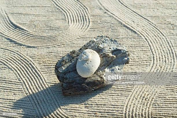 Stones stacked on top of driftwood on raked sand