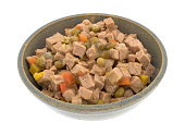 An old stoneware bowl filled with lamb dog food plus peas and squash isolated on a white background.