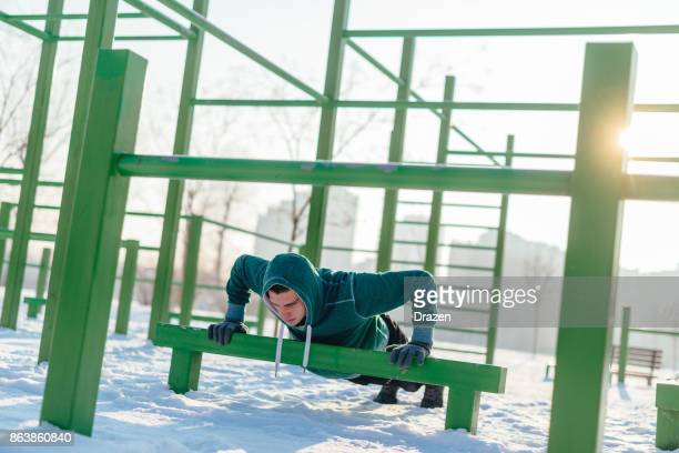 Stong athlete doing push ups in snow