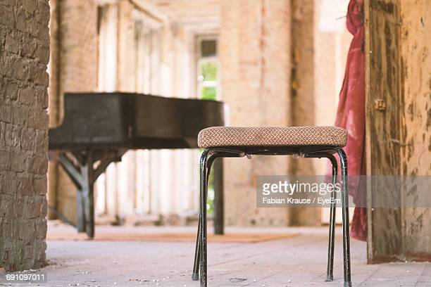 Stool By Grand Piano In Abandoned Room