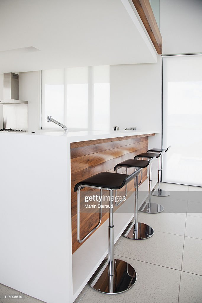 Stools at counter of modern kitchen : Stock Photo