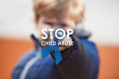 Child pressing stop child abuse awareness symbol on projection screen. Blue ribbon as sing of child abuse social issues.