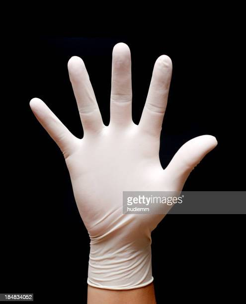 Stop! Man's hand wearing protective gloves isolated on black background