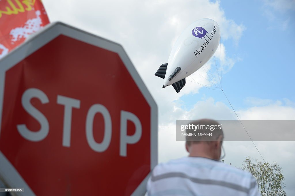 A stop sign and a balloon reading Alcatel-Lucent' are pictured during a protest on October 8, 2013 in Orvault, western France, in front of the plant of French-US telecom-equipment maker Alcatel-Lucent, after the group announced the cut of 10,000 jobs worldwide to reduce fixed costs by 15 percent in two years. The company said that 4,100 jobs would be cut in Europe, the Middle East and Africa by 2015, 3,800 in the Asia Pacific region, and 2,100 in North and South America.