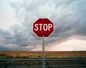 Stop sign by desert road with storm clouds