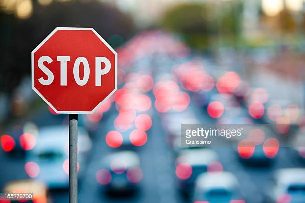 Stop sign with traffic and cars at rush hour