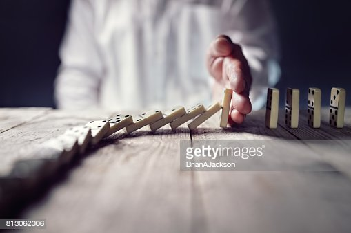 Stop the domino effect concept for business solution and intervention : Stock Photo