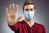 Stop the infection! Healthy man showing gesture 'stop'. Photo of man wear protective mask against infectious diseases and flu. Health care concept.