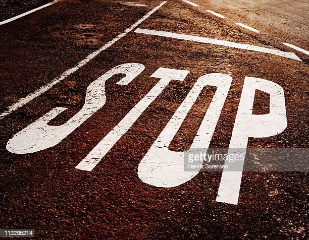 Stop warning printed on tarmac road
