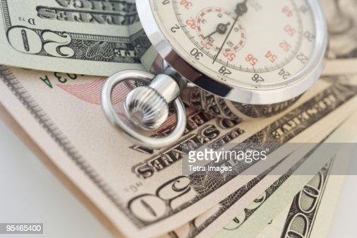 A stopwatch on top of fifty dollar bills