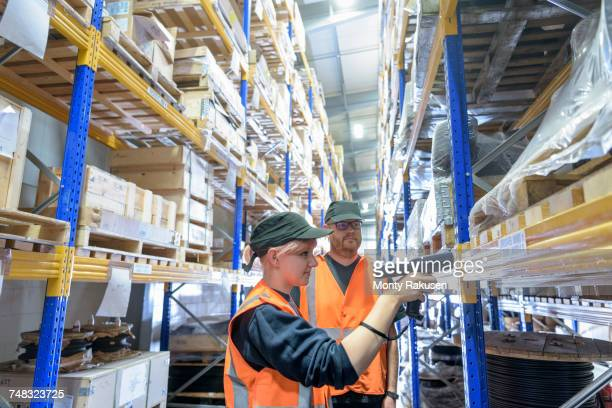 Storage workers scanning parts in train works warehouse