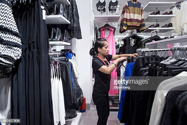 A store assistant arranges clothing in a Hennes Mauritz AB store at the Select Citywalk mall in the Saket area of New Delhi India on Friday Oct 2...