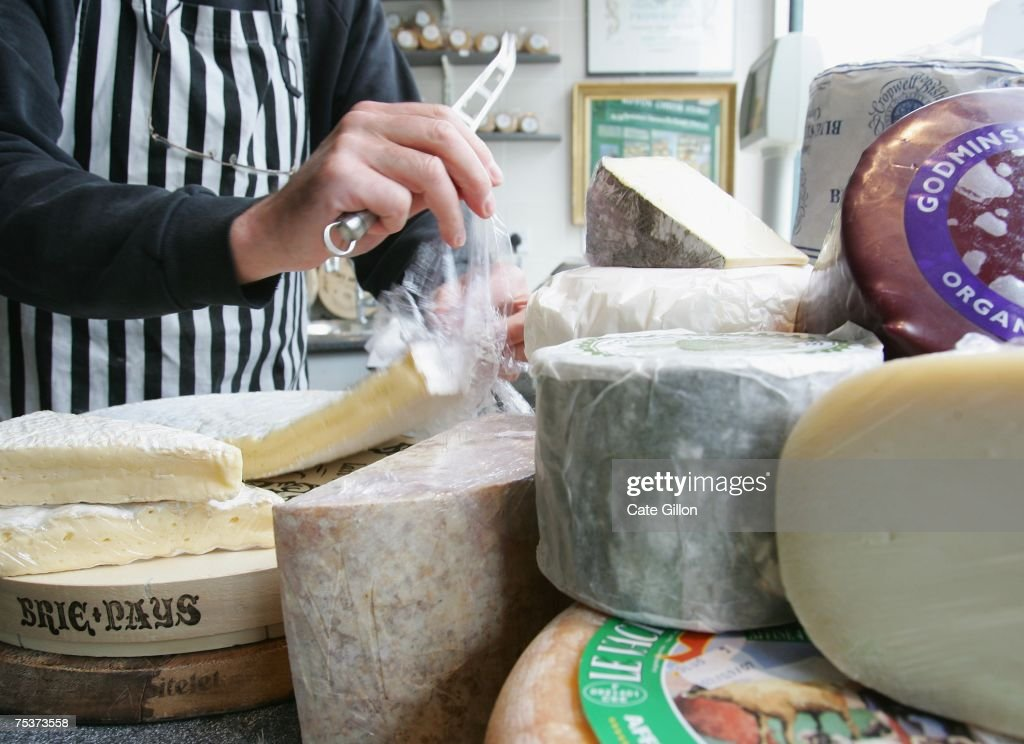 A store assistant cuts brie, which can contain between 45 and 60 percent fat, for a customer in a cheese store on July 12, 2007 in London, England. Government advisors are considering a tax on high fat foods to tackle obesity. Foods targeted include dairy products such as fatty cheese, full fat milk and fresh butter.