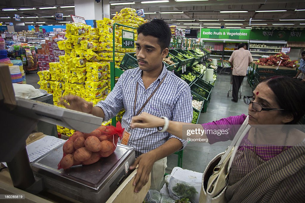 A store assistant helps a customer weigh a bag of potatoes in the vegetable section of the Big Bazaar Hypermarket store in Noida, India, on Monday, Sept. 9, 2013. Indias rupee fell, snapping the biggest four-day surge in 40 years, on concern slowing growth will deter inflows needed to reduce the current-account deficit. Photographer: Prashanth Vishwanathan/Bloomberg via Getty Images