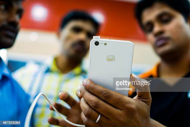 A store assistant right demonstrates a Micromax Informatics Ltd smartphone to customers at the company's Micromax World store in New Delhi India on...
