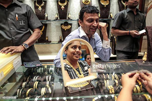 A store assistant serves a customer reflected in a mirror as she tries on gold jewelry in the Dwarkadas Chandumal Jewelers store in the Zaveri Bazaar...