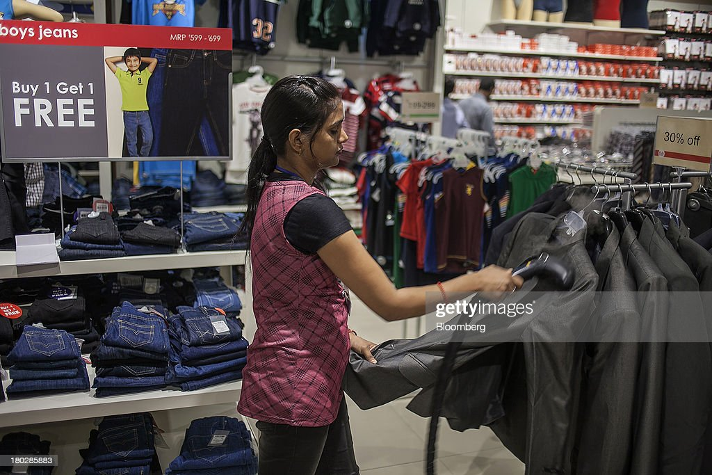 A store assistant steams a piece of clothing at the Fashion at Big Bazaar (FBB) section of the Big Bazaar Hypermarket store in Noida, India, on Monday, Sept. 9, 2013. Indias rupee fell, snapping the biggest four-day surge in 40 years, on concern slowing growth will deter inflows needed to reduce the current-account deficit. Photographer: Prashanth Vishwanathan/Bloomberg via Getty Images