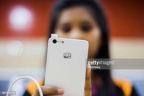 A store assistant takes a selfie while demonstrating a Micromax Informatics Ltd smartphone to customers unseen at the company's Micromax World store...