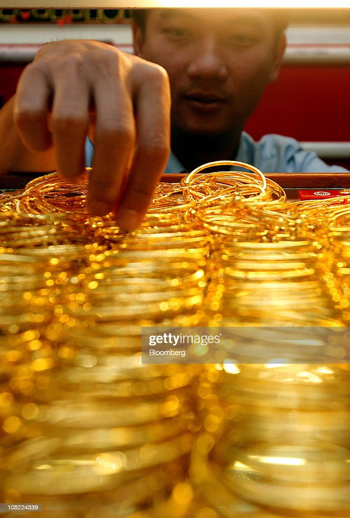 A store attendant arranges a display of gold jewelry at for Heng kunthea jewelry shop