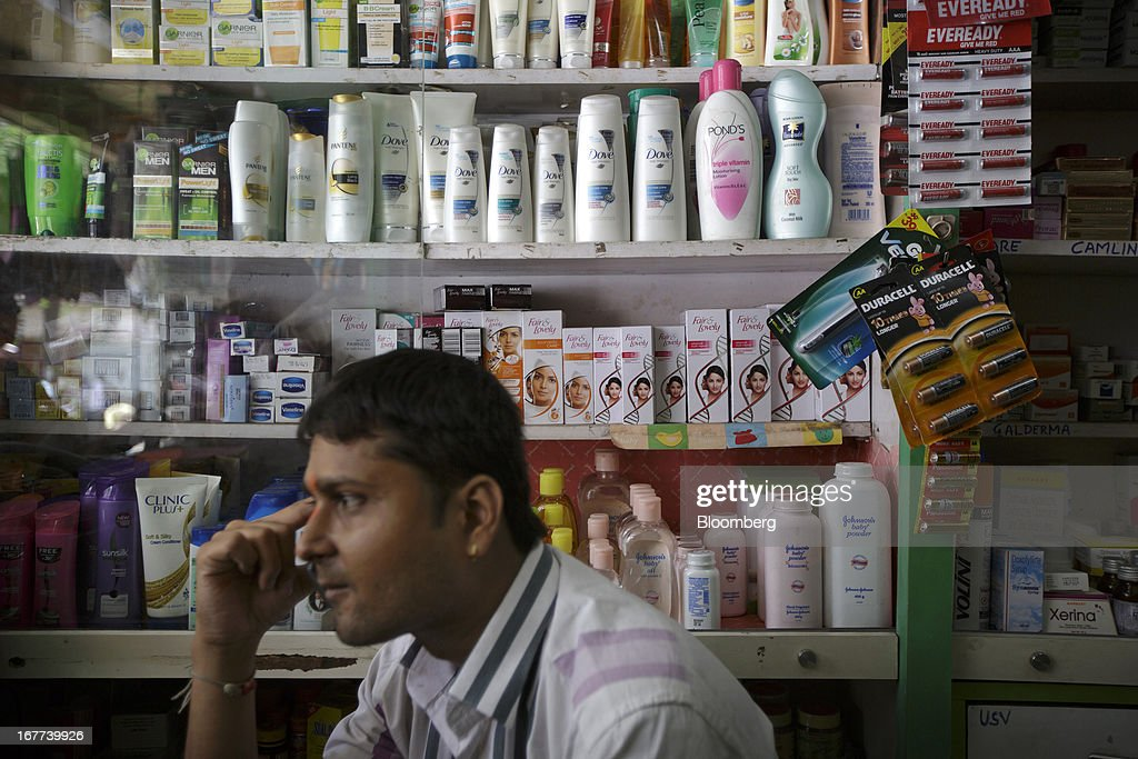 A store attendant sits in front of bottles of Hindustan Unilever Ltd. Dove shampoo and Fair & Lovely beauty products displayed at a store in Mumbai, India, on Saturday, April 27, 2013. Consumer goods maker Hiindustan Unilever is scheduled to report earnings today. Photographer: Kuni Takahashi/Bloomberg via Getty Images