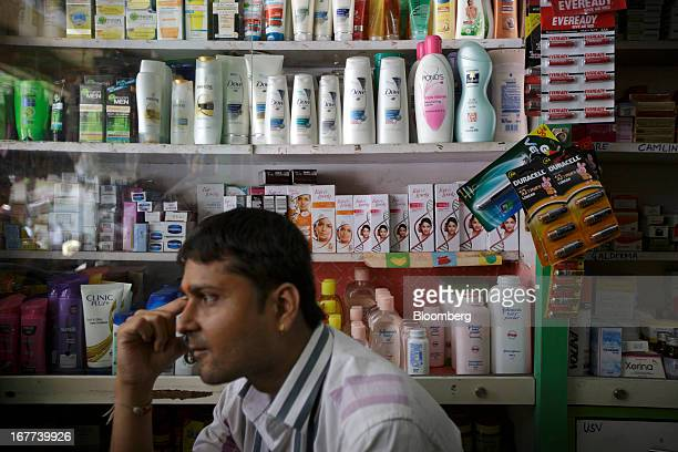 A store attendant sits in front of bottles of Hindustan Unilever Ltd Dove shampoo and Fair Lovely beauty products displayed at a store in Mumbai...