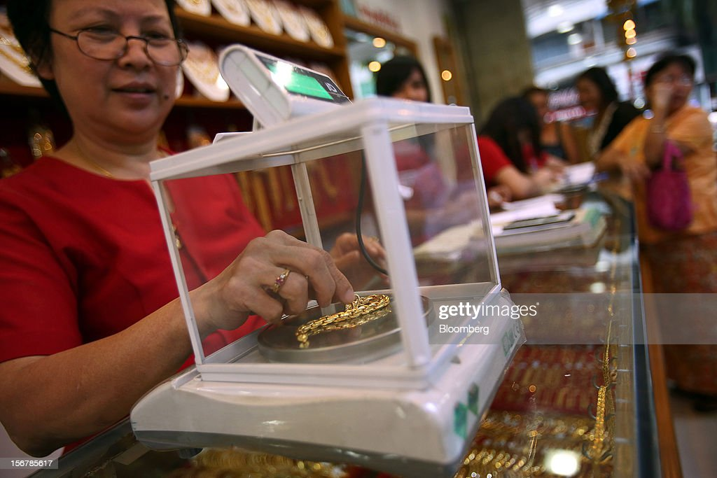 A store attendant weighs a gold bracelet for a customer at a jewelry store in Yangon, Myanmar, on Tuesday, Nov. 20, 2012. Myanmar's growth outlook has improved 'substantially' amid political reforms, which are expected to lead to a large influx of foreign investment, the Organization for Economic Cooperation and Development (OECD) said on Nov. 18. Photographer: Dario Pignatelli/Bloomberg via Getty Images