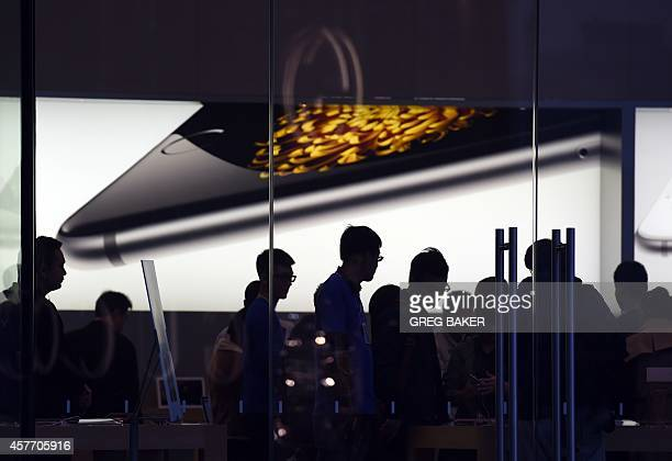 Store attendants help customers at an Apple store selling the iPhone 6 in Beijing on October 23 2014 During a trip to Shanghai last January Apple CEO...