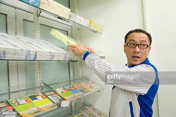 Store clerk arranging products