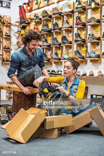 Store clerk helping a customer to try hiking boots