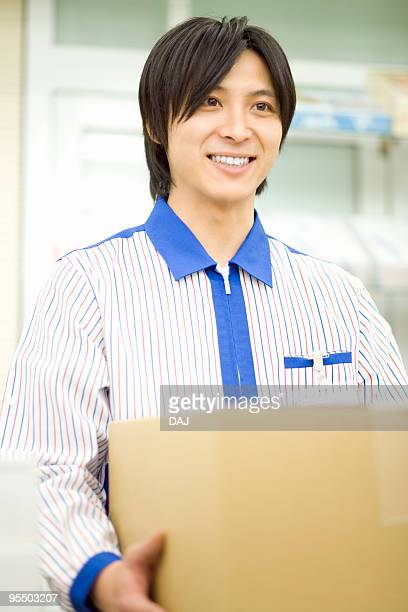 Store clerk holding cardboard box