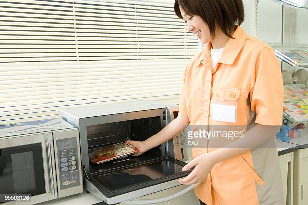 Store clerk putting food in microwave