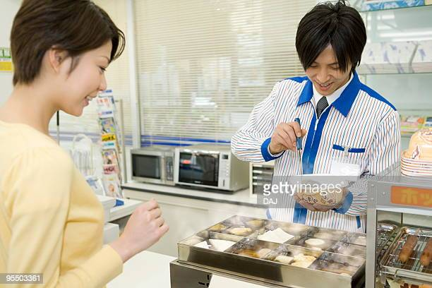 Store clerk scooping oden for young woman
