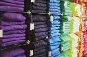 Store display of shirts stacked in rainbow order