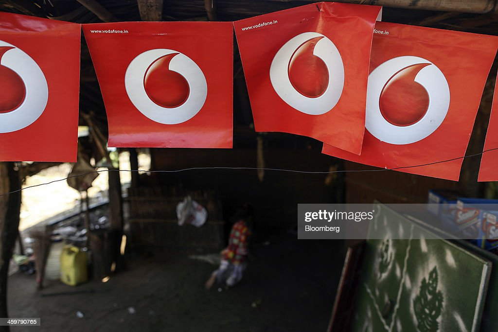 A store displays advertising for Vodafone Group Plc on Dahanu Road in Kainad, Maharashtra, India, on Saturday, Dec. 21, 2013. The construction of 600,000 kilometers (373,000 miles) of country roads, addition of 327 million rural phone connections and a rise in literacy to record levels since Prime Minister Manmohan Singh took office in 2004 has helped double the growth rate of Indias food output. Photographer: Dhiraj Singh/Bloomberg via Getty Images