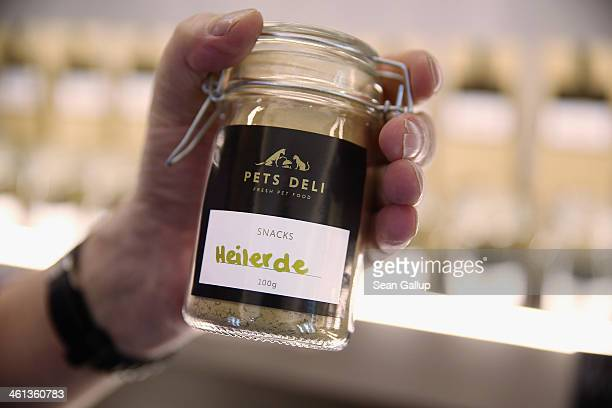 A store employee displays a container of 'healing earth' which is a mixture of subtances that neutralize toxins in the digestive tract of a dog at...