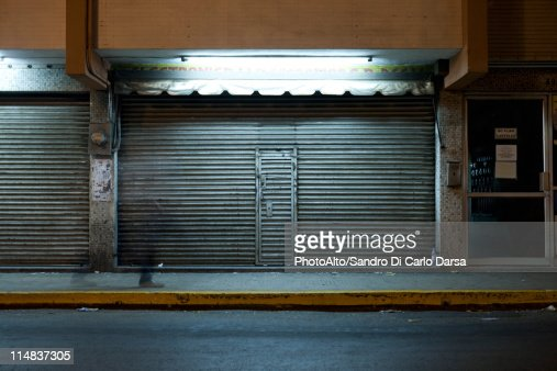 Store front with locked roll-up door at night