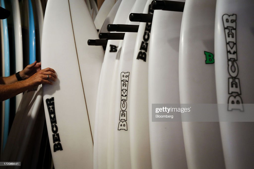 Store manager Bob Rich arranges surfboards displayed for sale at the Becker Surf retail store, purchased by Billabong in 2010, in Hermosa Beach, California, U.S., on Monday, July 1, 2013. The U.S. Census Bureau is scheduled to release factory orders figures on July 2. Photographer: Patrick T. Fallon/Bloomberg via Getty Images