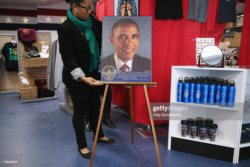 Store manager Liz Matory prepares merchandise, including this comemorative poster by artist Chuck Close, for the grand opening of the Presidential Inaugural Committee's store near the intersection of 11th and F Streets NW January 11, 2013 in Washington, DC. A variety of merchandise will be for sale until the January 21 inaugural ceremony, from buttons and water bottles to handbags and limited edition coin sets.
