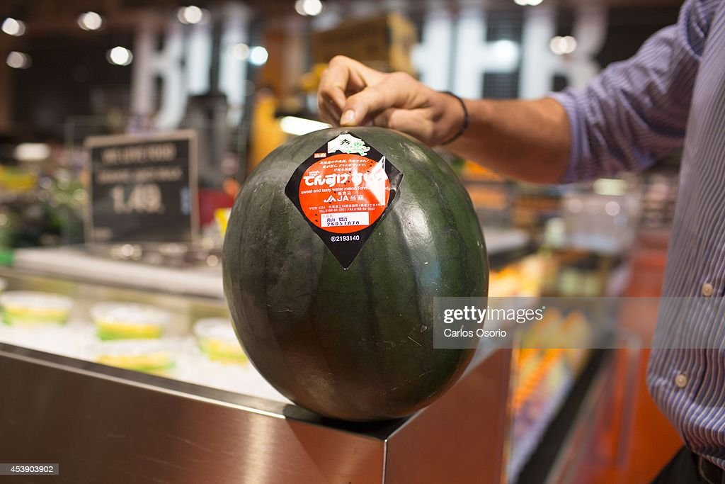 TORONTO, ON - AUGUST 20 - Store Manager of Maple Leafs Gardens Loblaws George Mpantigiorgis poses for a photograph with a Densuke watermelon from Japan. The fruit is being sold for $199.99. August 20, 2014.